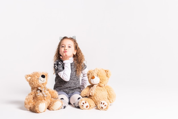Little girl with bear standing on white