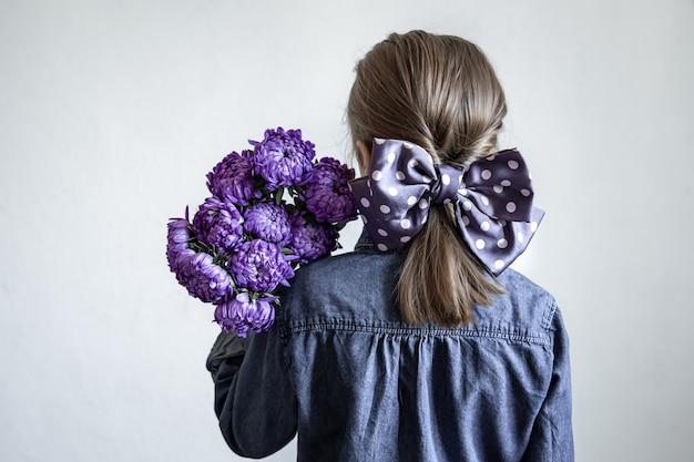 Little girl with a beautiful bow on her hair holds a bouquet of blue chrysanthemums, back view.