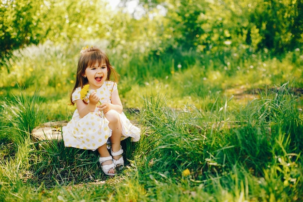 A little girl with beautiful long hair and in a yellow dress is playing in the summer park