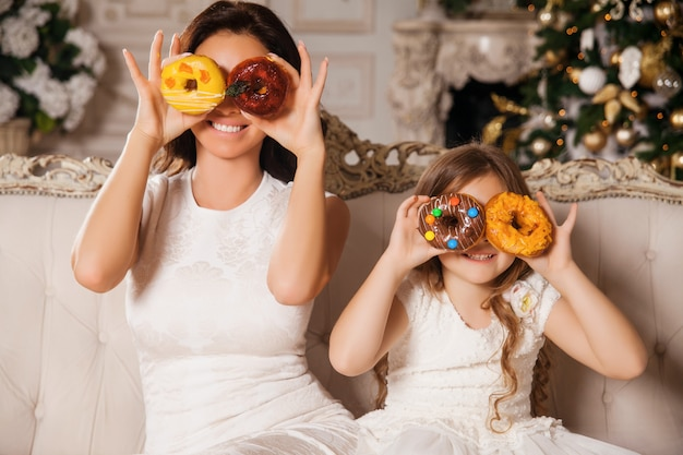Little girl with beautiful mother having fun with donuts