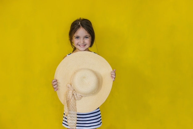 A little girl with a big beach hat in her hands on a yellow wall.the girl hides behind her hat