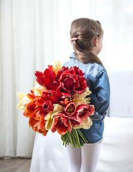 Little girl with a big bouquet of tulips