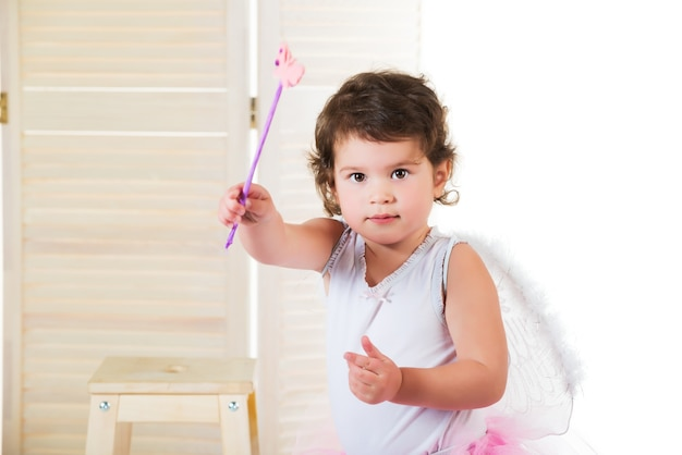 Little girl with big brown eyes, dressed in fairy costume, hand raised up and holds magic wand