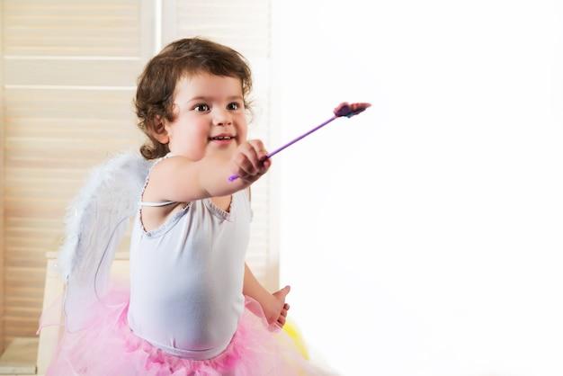Маленькая девочка с большими карими глазами, одетая в костюм феи, подняла руку и держит волшебную палочку