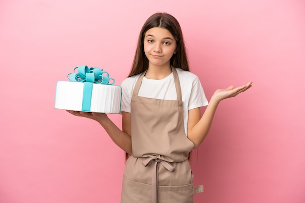 Little girl with a big cake over isolated pink background having doubts while raising hands