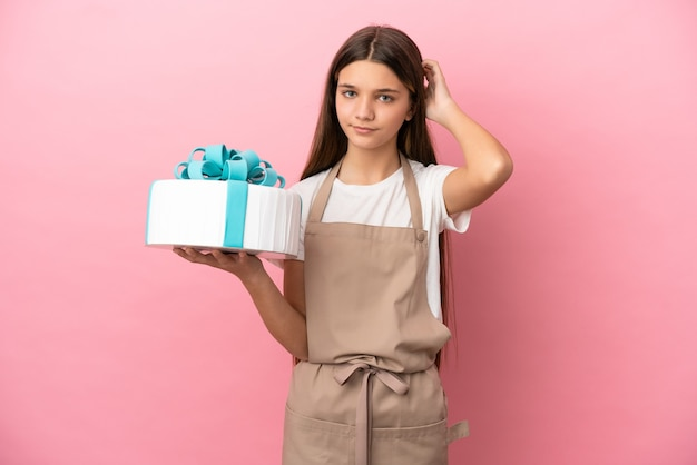 Little girl with a big cake over isolated pink background having doubts