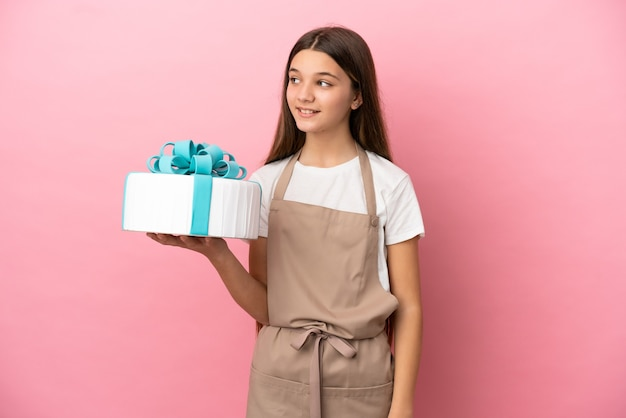 Little girl with a big cake over isolated pink background looking to the side and smiling
