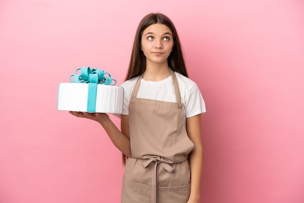 Little girl with a big cake over isolated pink background and looking up