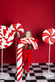 Little girl with a big christmas candy cane on an isolated red wall. huge christmas candies. sweets
