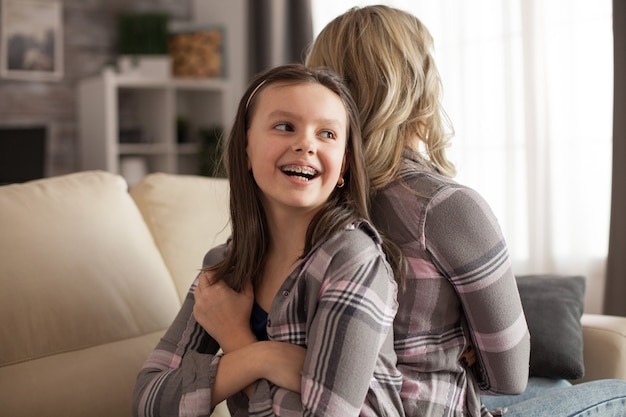 Little girl with a big smile and braces sitting back to back with her mother upset on her. disobedient kid