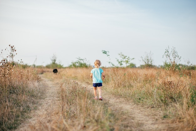 Little girl with black dog walking on the field back to camera in hot summer evening.
