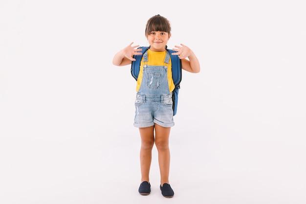 青いダンガリーとtシャツを着た黒い髪の少女、白い背景の上に、彼女の手で手を振って、学校に戻る準備ができているバックパックを持っています。