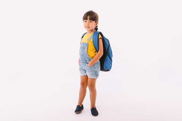 青いダンガリーとtシャツに身を包んだ黒い髪の少女、白い背景に学校に戻る準備ができているバックパック