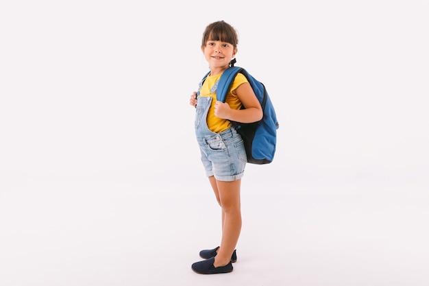 デニムのオーバーオールと青いtシャツを着た黒い髪の少女、白い背景の上に、彼女の側で、学校に戻る準備ができているバックパックを持っています
