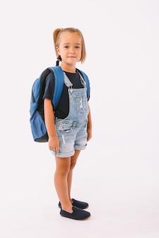 파란 바지와 티셔츠를 입은 금발 머리를 가진 어린 소녀, 흰색 배경에 학교로 돌아갈 준비가 된 배낭