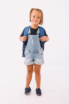 青いダンガリーとtシャツに身を包んだブロンドの髪の少女、白い背景で学校に戻る準備ができてバックパック