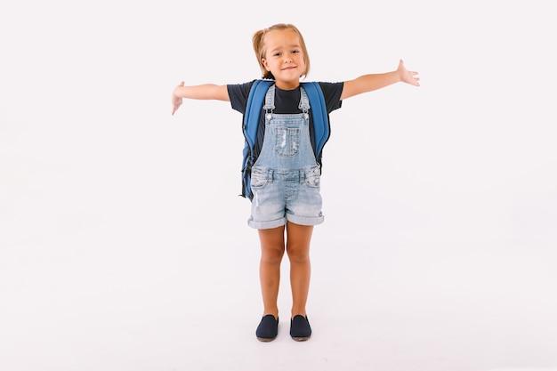 デニムのオーバーオールと青いシャツを着たブロンドの髪の少女、学校に戻る準備ができているバックパック、腕を開いて、とても幸せで、白い背景に