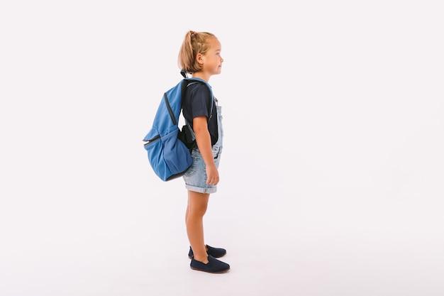 デニムのオーバーオールと青いtシャツを着たブロンドの髪の少女、白い背景の上に、彼女の側で、学校に戻る準備ができているバックパックを持っています