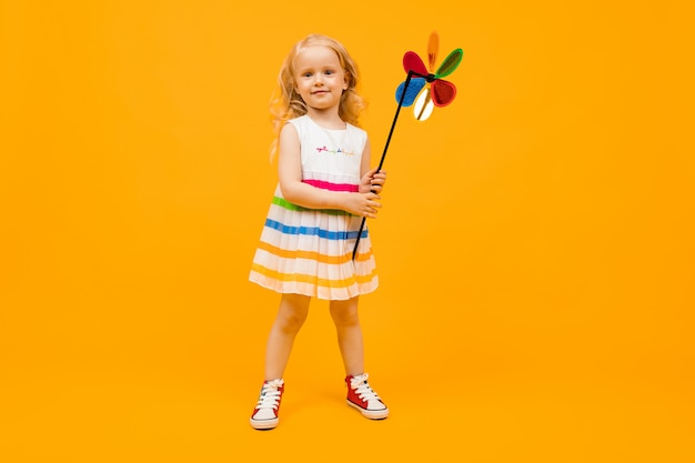 Little girl with blond hair holds a round toy propeller on a yellow background