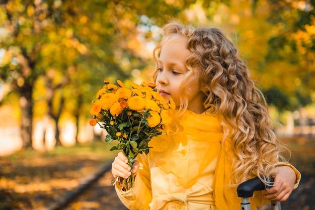 花とスーツケースの秋の背景にブロンドの髪を持つ少女
