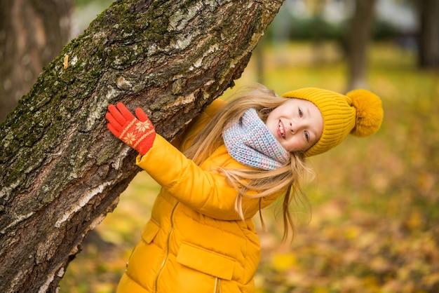 Маленькая девочка со светлыми волосами в осеннем парке