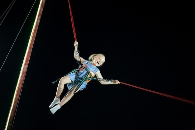 Маленькая девочка со светлыми волосами в воздухе на катапульте на фоне черного неба. веселые летние каникулы.