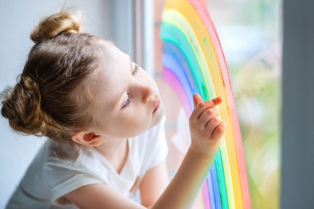 A little girl with blond hair looks at a rainbow on the window.