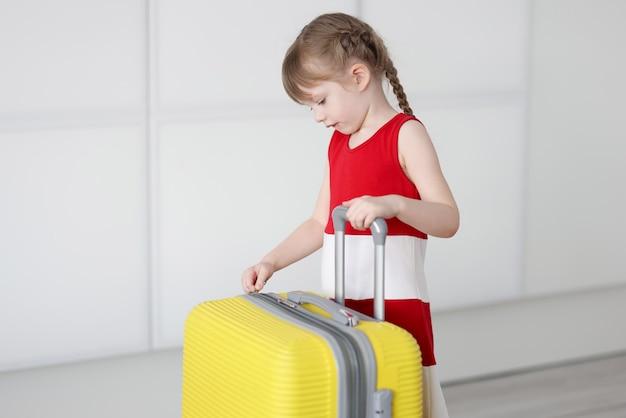 ブロンドの髪の少女が黄色いスーツケースを開く