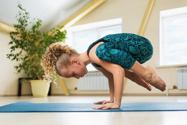 Little girl with blond hair practicing yoga doing handstand exercise kakasana or crow pose on a gymnastic mat