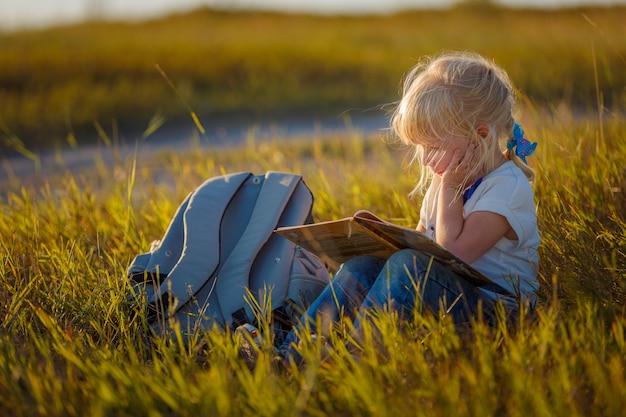 自然の本とブロンドの髪を持つ少女。小児発達。