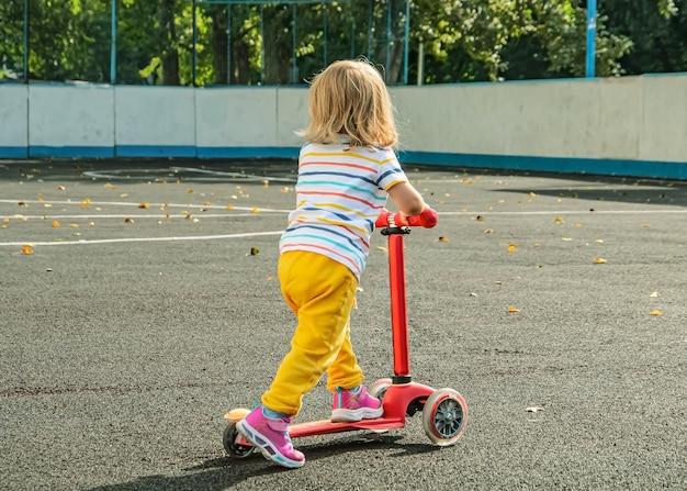 Маленькая девочка со светлыми волнистыми волосами в спортивной одежде с самокатом на огороженной спортивной площадке.