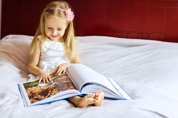 Little girl with blonde hair reading book on the bed