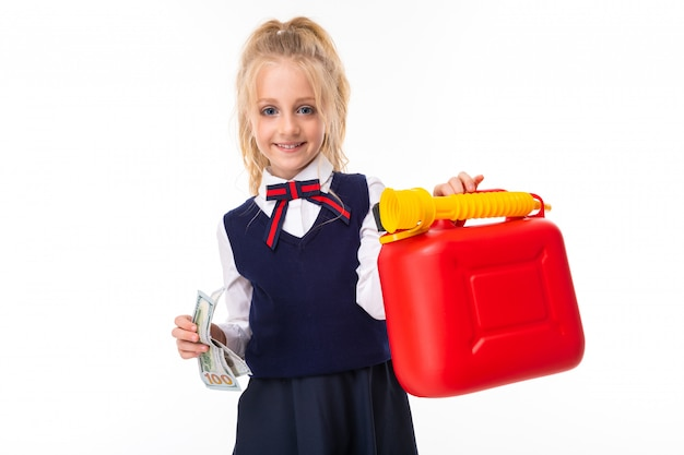 A little girl with blonde hair stuffed in a horse tail, large blue eyes and a cute face holds money and a toy can.