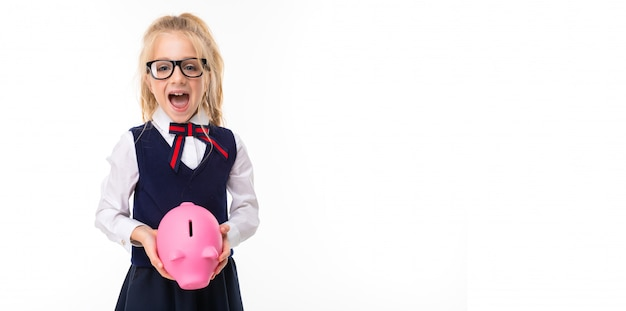 A little girl with blonde hair stuffed in a horse tail, large blue eyes and a cute face in square black glasses with a moneybox.