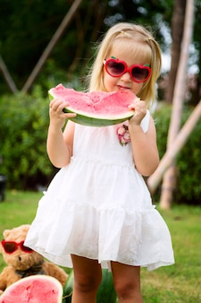 Little girl with blonde hair in sunglasses eating watermelon on the park, next sitting teddy bear