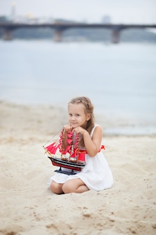 Little girl with blonde hair in white dress holding ship with scarlet sails. child sit on seashore, holds a toy sailboat in his hands.