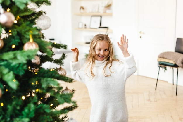 Little girl with blonde hair in a white sweater playing near the christmas tree, laughing, smiling,