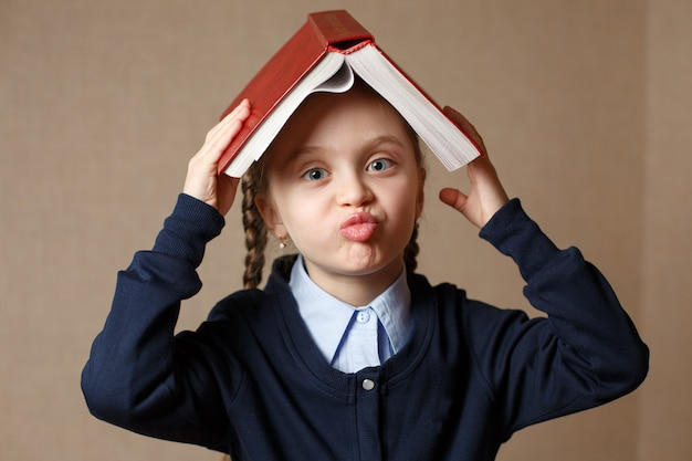 Little girl with a book over her head