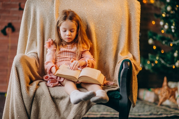 Little girl with book sitting in chair by christmas tree