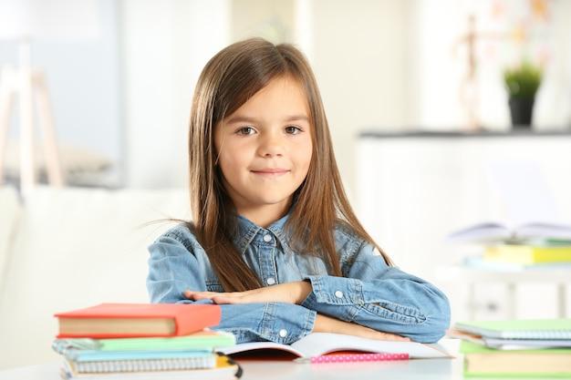 テーブルに座っている本を持つ少女
