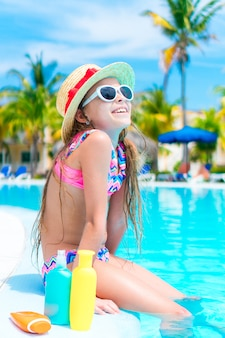 Little girl with bottle of sun cream sitting on the edge of swimming pool