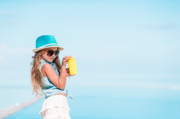 Little girl with bottle of sun cream in swimming pool