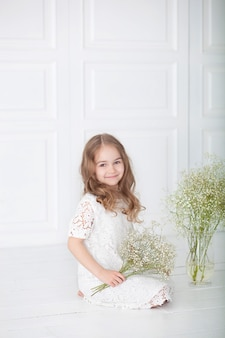 Little girl with a bouquet of gypsophila. portrait of a charming girl with blond hair in a white dress holding flowers. cute baby with a bouquet.