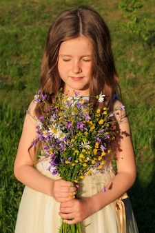Little girl with a bouquet of wildflowers and eyes closed
