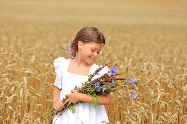 Little girl with a bouquet of wildflowers in her hands in a wheat field.