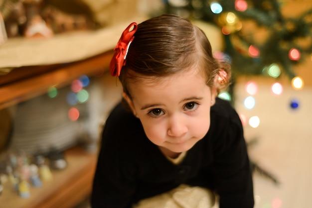 Bambina con fiocco nei capelli a casa con decorazioni e luci di natale sfocato.