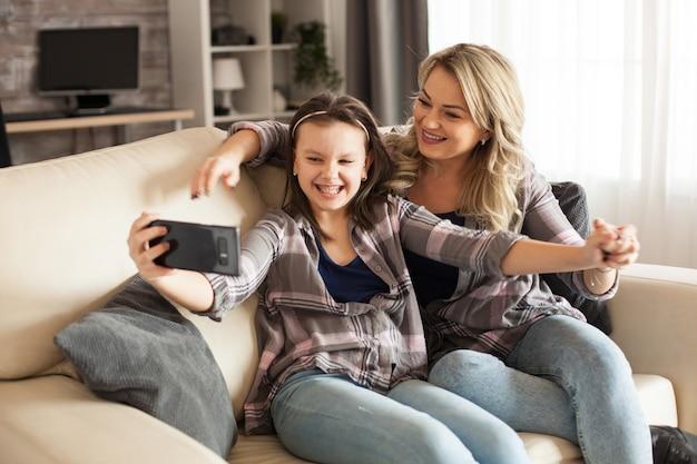 中かっこを持った少女と、リビングルームのソファに座って自分撮りをしている母親。