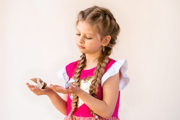A little girl with braids and a pink dress holds two paper birds.