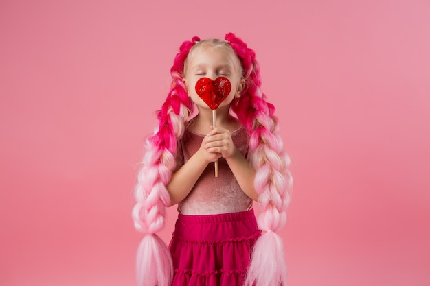 Little girl with braids of pink kanekalon holds a heart-shaped lollipop on a pink background