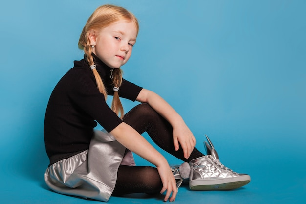 Little girl with braids in stylish clothes on blue